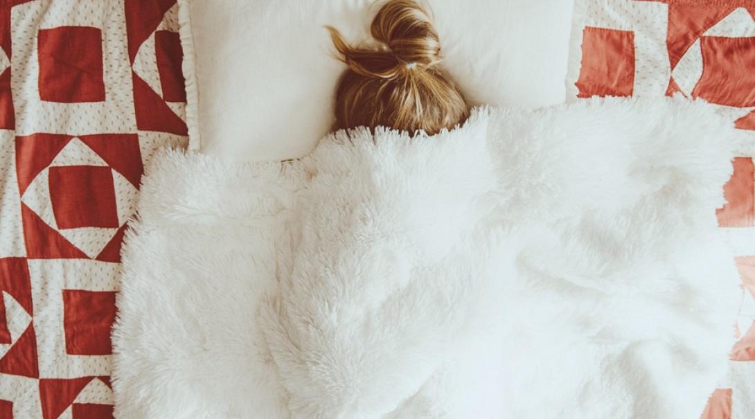 腹痛でベッドにうずくまる女性